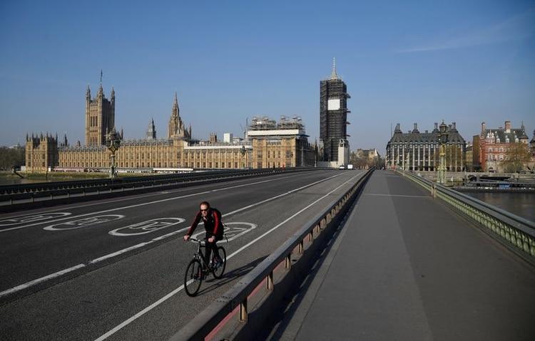 Un ciclista pasa por el puente de Westminster mientras continúa la propagación de la enfermedad coronavirus (COVID-19), Londres, Reino Unido, 10 de abril de 2020. REUTERS/Toby Melville