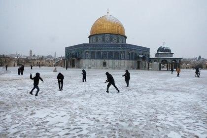 La gente juega junto a la Cúpula de la Roca en el complejo conocido por los judíos como el Monte del Templo y por los musulmanes como el Noble Santuario durante una mañana nevada en la Ciudad Vieja de Jerusalén, el 18 de febrero de 2021. REUTERS / Ammar Awad