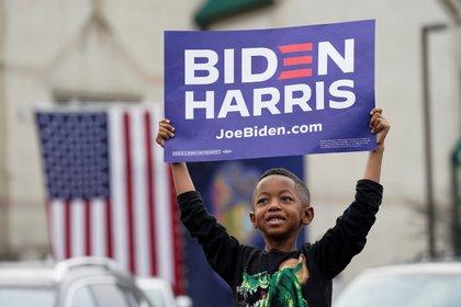 Un niño sostiene un cartel mientras asiste al evento de campaña del candidato presidencial demócrata estadounidense Joe Biden en Filadelfia. REUTERS/Kevin Lamarque