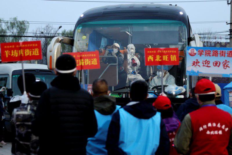 Varias personas que regresan procedentes de la provincia de Hubei, el origen del brote de coronavirus en China, llegan a un punto de reunión mientras los trabajadores de sus comunidades esperan para recogerlos, en Pekín, China, el 25 de marzo de 2020. cnsphoto vía REUTERS.