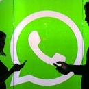 People are seen as silhouettes as they check mobile devices whilst standing against an illuminated wall bearing WhatsApp Inc's logo in this arranged photograph in London, U.K., on Tuesday, Jan. 5, 2016. WhatsApp Inc. offers a cross-platform mobile messaging application that allows users to exchange messages. Photographer: Chris Ratcliffe/Bloomberg