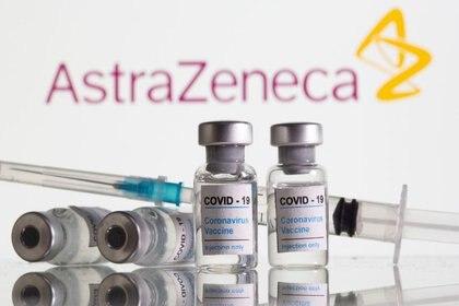 """FOTO DE ARCHIVO: Frascos con la etiqueta """"COVID-19 Vacuna del coronavirus"""" y jeringuilla delante del logotipo de AstraZeneca en una ilustración tomada el 9 de febrero de 2021. REUTERS/Dado Ruvic/Ilustración"""