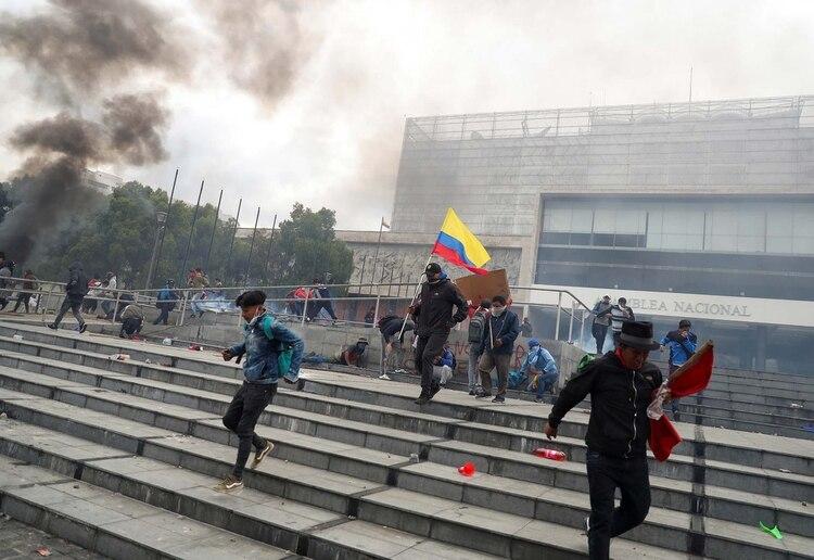 Manifestantes huyen de la represión policial en la escalinata del Parlamento en Quito (REUTERS/Ivan Alvarado)