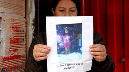 Una mujer sostiene un papel con la fotografía de la niña Yuliana, cuando todavía era buscada