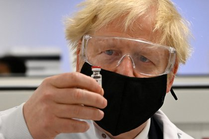 El premier británico Boris Johnson observa un vial de la candidata de Oxford y Astrazeneca (Reuters)