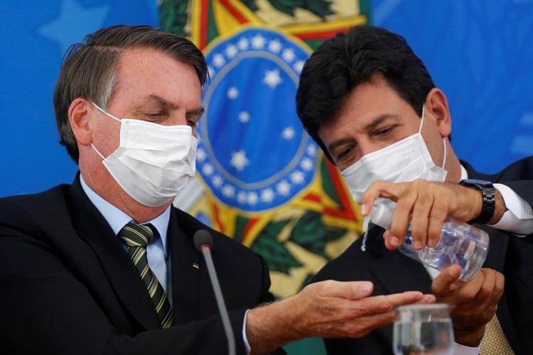 Jair Bolsonaro y el ministro de Salud, Luiz Henrique Mandetta, con máscaras faciales, se higienizan las manos durante una conferencia de prensa el 18 de marzo de 2020. (REUTERS/Adriano Machado)