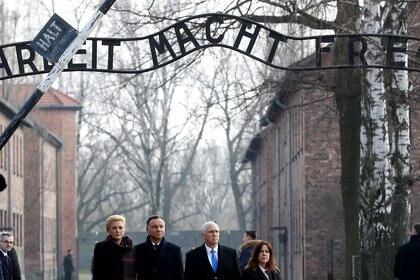 El vicepresidente estadounidense Mike Pence con su esposa Karen y el presidente de Polonia, Andrzej Duda, con la primera dama Agata Kornhauser-Duda se paran en la puerta de entrada del campo de concentración y exterminio nazi Auschwitz el 15 de febrero de 2019. (REUTERS / Kacper Pempel)
