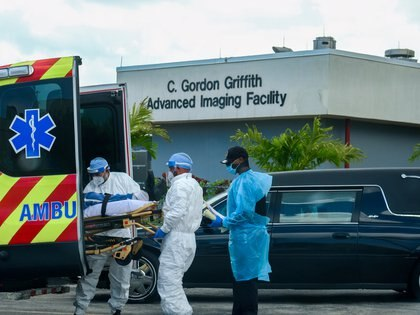 Emergency Medical Technicians (EMT) arrive with a patient while a funeral car begins to depart at North Shore Medical Center where the coronavirus disease (COVID-19) patients are treated, in Miami, Florida, U.S. July 14, 2020. REUTERS/Maria Alejandra Cardona