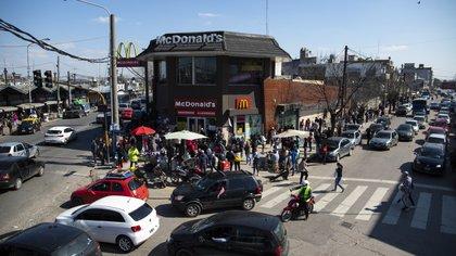 Aglomeración de gente frente a un local de comidas rápidas, cerca de la estación de tren. Av. Luro y Luque Honorio, en Gregorio de Laferrere, La Matanza
