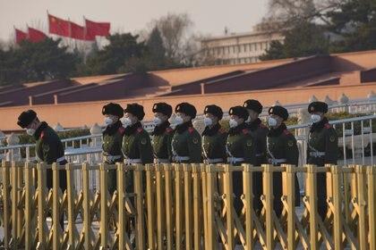 Oficiales de las fuerzas de seguridad montan guardia frente a la Puerta de Tiananmen, en Beijing, cubiertos con máscaras (REUTERS/Stringer)