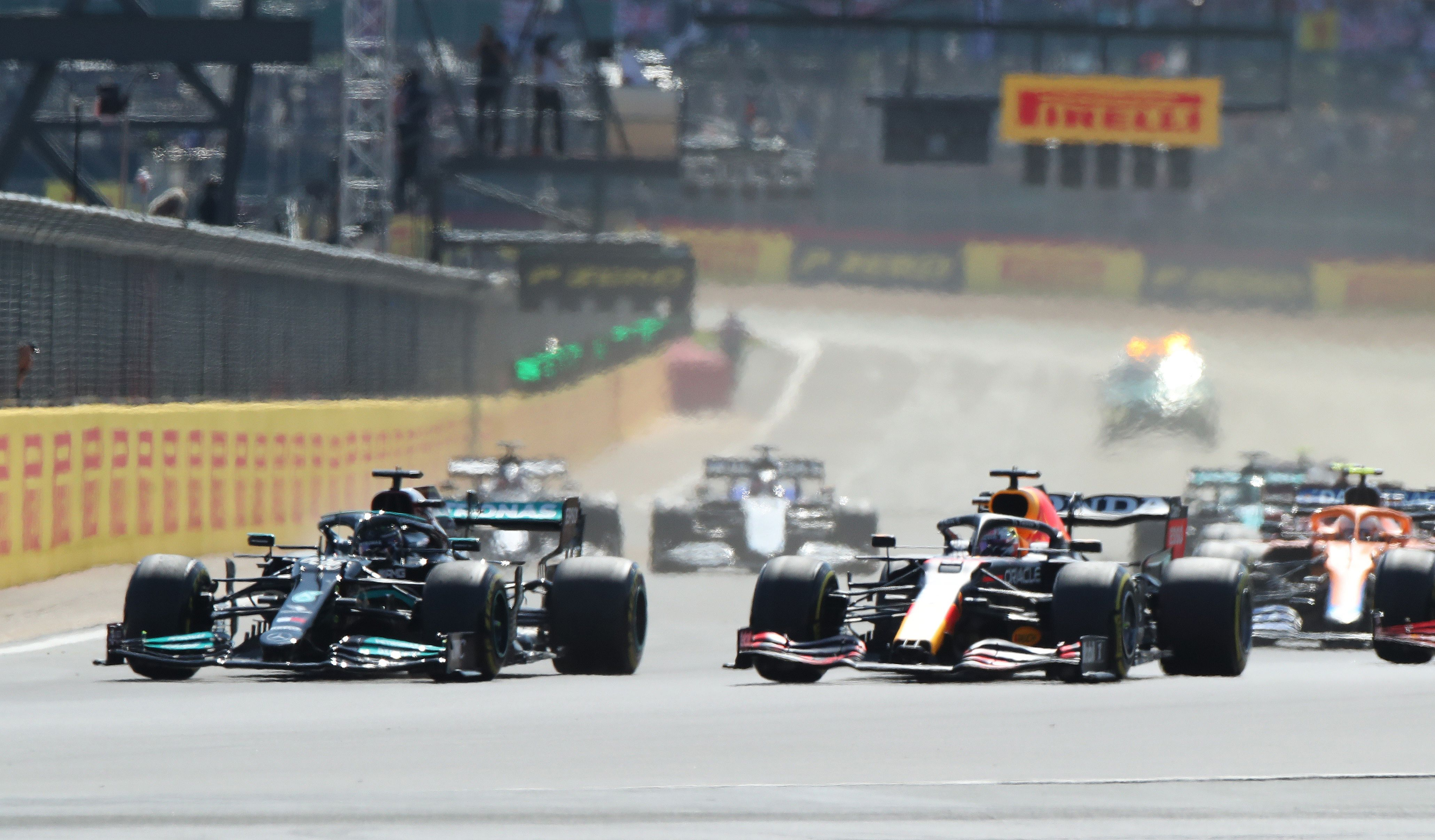 Formula One F1 - British Grand Prix - Silverstone Circuit, Silverstone, Britain - July 18, 2021 Red Bull's Max Verstappen leads at the start of the race ahead of Mercedes' Lewis Hamilton REUTERS/Peter Cziborra