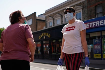 Women wearing face masks speak to eachother, as the spread of the coronavirus disease (COVID-19) continues, at North End Road in London, Britain, April 24, 2020. REUTERS/Henry Nicholls