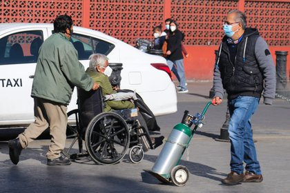 Decenas de personas esperan en uno de los dos puntos habilitados para rellenar tanques de oxígeno de manera gratuita a los pacientes de la Covid-19 que completan la recuperación en sus casas hoy, en Ciudad de México (México). (Foto: EFE)