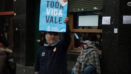 """Una persona sin techo es vista detrás de un cartel con la leyenda """"Toda Vida Vale"""" (Adrián Escandar)"""