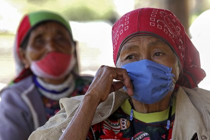 Elderly Wixarica indigenous women wait to be inoculated with the CanSino Biologics vaccine against COVID-19 at a vaccination center installed in the town of Nuevo Colonia, in Mezquitic, Jalisco state, Mexico, on April 16, 2021. - After walking for up to four hours from their communities, besieged by drug traffickers, elderly Wixarica indigenous people were vaccinated against COVID-19 at a remote region in the east of Mexico. (Photo by ULISES RUIZ / AFP)