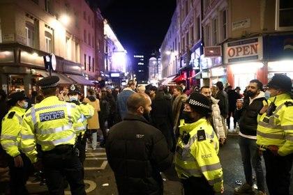 Un oficial de la Policía Metropolitana habla con un hombre mientras la gente celebra en una calle del Soho, mientras se alivian las restricciones de la enfermedad por coronavirus (COVID-19), en Londres, Gran Bretaña, el 12 de abril de 2021. REUTERS / Henry Nicholls