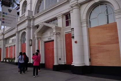 People walk by a store boarded up in anticipation of violence as a result of the upcoming US presidential election, in Beverly Hills, November 1, 2020   Personas caminan frente a un comercio tapiado en Los Ángeles. Foto:  Chris DELMAS / AFP