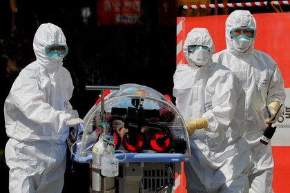 Trabajadores médicos llevan a un paciente en una camilla de aislamiento de presión negativa a una instalación del Hospital Universitario Nacional de Kyungpook en Daegu, Corea del Sur, el 6 de marzo de 2020 (Reuters/ Kim Kyung-Hoon)