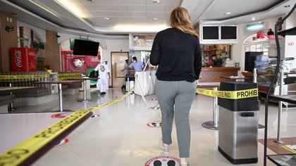 A woman enters a pizzeria to pick up an order, in Mexico City on June 30, 2020 during the COVID-19 pandemic. - Starting this week Mexico City is allowing the reopening of shops, street markets and athletic complexes but with limited capacity and hours. Hotels and restaurants in the capital will reopen at about 30% seating capacity. (Photo by ALFREDO ESTRELLA / AFP)