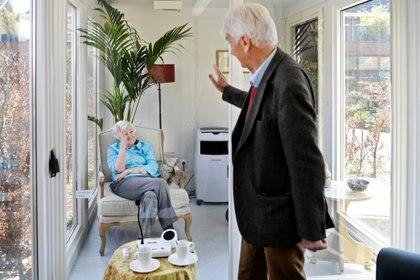 Un hombre visita a su esposa en un centro de atención a personas mayores con demencia, en una casa de cristal hecha especialmente para combatir la soledad causada por la prohibición de visitas debido al brote de coronavirus (COVID-19) en Wassenaar, Holanda, el 9 de abril de 2020. (REUTERS/Piroschka van de Wouw)