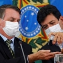 Brazil's President Jair Bolsonaro and Minister of Health Luiz Henrique Mandettas, wearing protective face masks, sanitize their hands during a news conference to announce measures to curb the spread of the coronavirus disease (COVID-19) in Brasilia, Brazil March 18, 2020. REUTERS/Adriano Machado