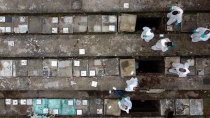 01/04/2021 Los empleados del cementerio de Nova Cachoeirinha, el segundo más grande de Sao Paulo (Brasil), retiran los huesos de las tumbas antiguas para hacer sitio a los nuevos muertos por la COVID-19. POLITICA  DARIO OLIVEIRA / ZUMA PRESS / CONTACTOPHOTO