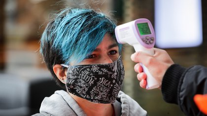Un trabajador toma la temperatura a una persona para entrar a un centro comercial, en Montevideo (Uruguay) (EFE/Raúl Martínez)