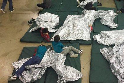 Niños detenidos por intentar entrar al país sin autorización descansan en una de las jaulas en el centro de McAllen, Texas, el domingo 17 de junio de 2018. (Oficina de Aduanas y Protección Fronteriza vía AP)