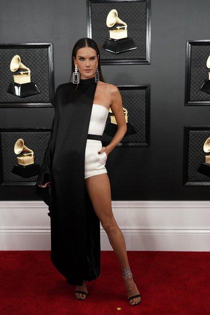 Alessandra Ambrosio, el ángel de Victoria's Secret lució en la alfombra roja de los Grammy un diseño asimétrico en blanco y negro. Un mono blanco con bolsillos que completó con aros XL geométricos y sandalias con pulsera plateadas y negras