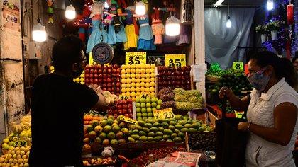 ACOMPAÑA CRÓNICA: MÉXICO ALIMENTOS - AME5948. CIUDAD DE MÉXICO (MÉXICO), 03/08/2020.- Un comerciante vende fruta el 31 de julio de 2020, en la Central de Abastos, en Ciudad de México (México). Millones de mexicanos está en situación de pobreza y el hambre se agudiza debido a la pandemia de coronavirus. El Banco de Alimentos es uno de los organismos que lucha contra esta lacra dando, además de alimentos, educación nutricional a quienes más lo necesitan. EFE/ Jorge Núñez