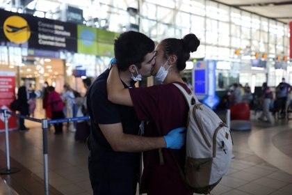 Una pareja se saca las mascarillas para besarse en el aeropuerto de Santiago de Chile (Reuters)