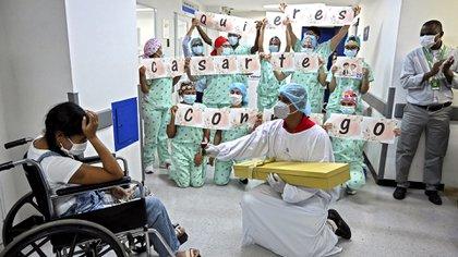 """Jefferson Riascos se arrodilla para pedirle a Diana Paola Angola, que se recuperó de coronavirus, que sea su esposa mientras que médicos y enfermeras de la clínica sostienen letras que forman la frase """"¿quieres casarte conmigo?""""en la clínica Versalles en Cali Colombia. (Photo by Luis ROBAYO / AFP)"""