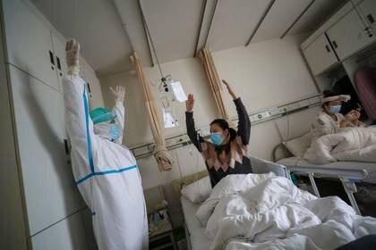 Un trabajador del equipo médico con traje protector muestra a una paciente los ejercicios de rehabilitación en una sala del Hospital de la Cruz Roja en Wuhan, China, el epicentro del nuevo brote de coronavirus. 24 de febrero de 2020. Imagen obtenida por un tercero. China Daily vía REUTERS.
