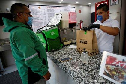 Un vendedor, con una máscara protectora, entrega comida a un trabajador de Uber Eats, mientras continúa el brote de la enfermedad por COVID-19 (Foto: Reuters)