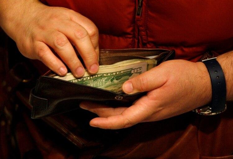 Un cliente de Macy's abre su billetera en una caja registradora durante el Black Friday en Nueva York (REUTERS/Jessica Rinaldi)
