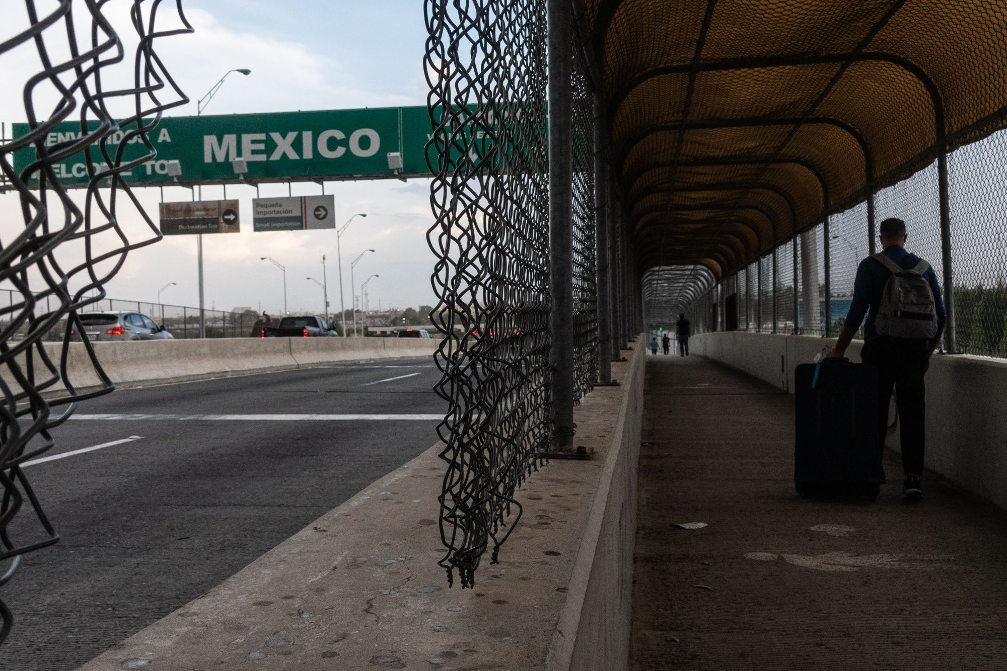 A pedestrian pulls a suitcase while walking along the Puente Internacional Cordova de las Americas (Puente Libre) bridge towards Ciudad Juarez, Chihuahua state, Mexico from El Paso, Texas, U.S., on Tuesday, Aug. 27, 2019. Poverty and violence—and the pull of the world's richest economy—are driving people north. At the border, they're met by a new regime of tightened security and laws, imposed by Trump in tandem with his Mexican counterpart, Andres Manuel Lopez Obrador, also known as AMLO. Photographer: Cesar Rodriguez/Bloomberg