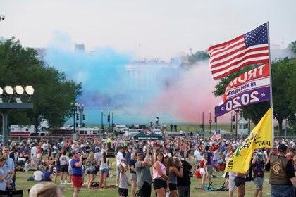 Un partidario del presidente Donald Trump sostiene una bandera de los Estados Unidos y una bandera de la campaña de reelección del mandatario durante las celebraciones del Día de la Independencia en Washington, Estados Unidos, el 4 de julio de 2020. REUTERS/Joshua Roberts
