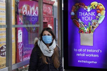Una mujer espera por el transporte público en Dublín, junto a un cartel de agradecimiento al personal sanitario (Reuters)