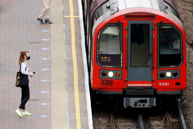 Una mujer con mascarilla en una plataforma en la estación de North Acton, Londres, Gran Bretaña.