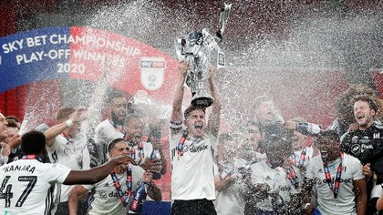 Soccer Football - Championship Play-Off Final - Brentford v Fulham - Wembley Stadium, London, Britain - August 4, 2020  Fulham's Tom Cairney lifts the trophy as he celebrates promotion to the premier league with teammates after winning the match, as play resumes behind closed doors following the outbreak of the coronavirus disease (COVID-19)  Action Images via Reuters/Matthew Childs