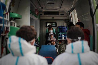 Una mujer con su pequeño hijo es trasladado en una ambulancia luego de dar positivo en un testeo de coronavirus en Villa Azul, este martes, en la Provincia de Buenos Aires (Argentina). EFE/Juan Ignacio Roncoroni
