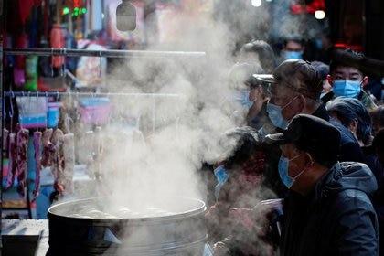 Personas con mascarillas comprando en un mercado callejero de Wuhan,