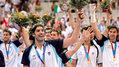 Luis Scola encabeza a la Generación Dorada en el podio de Atenas 2004 (AFP PHOTO/ADRIAN DENNIS)