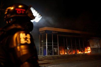 Un miembro de la policía antidisturbios fue registrado este jueves al observar el incendio de una sede bancaria, durante la segunda jornada de protestas violentas por la muerte del abogado Javier Ordóñez a manos de varios policías en Bogotá, en Cali (Colombia). EFE/Ernesto Guzmán Jr