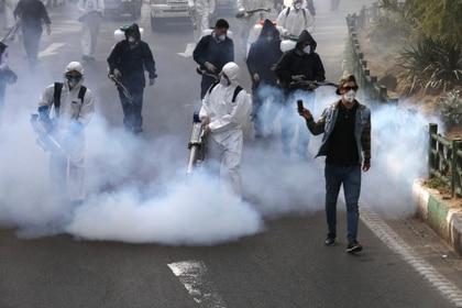 Bomberos desinfectando una plaza en Teherán (AP Foto/Vahid Salemi)