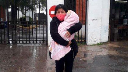La mujer caminó bajo la lluvia con uno de sus bebés para lograr que se llevaran el cuerpo