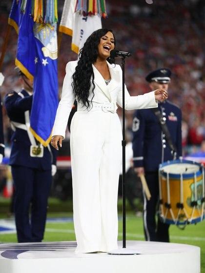 Demi Lovato lució para interpretar el Himno de los Estados Unidos antes de comenzar el partido un total white look sastrero, de una única pieza firmada por el diseñador Sergio Hudson
