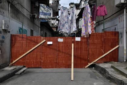 Tablas que bloquean la entrada a una zona residencial en Wuhan, el 4 de marzo de 2020 (REUTERS/Stringer)