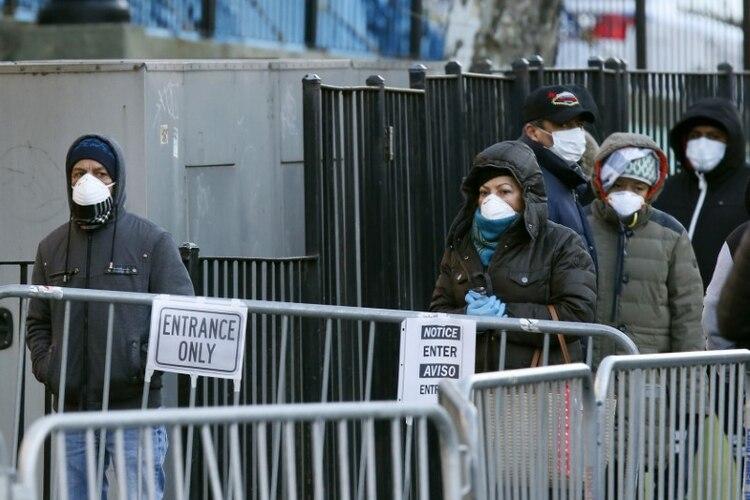 Personas utilizando mascarillas hacen fila para realizarse pruebas por coronavirus fuera del Hospital Center, en el vecindario de Queens, Nueva York (REUTERS/Stefan Jeremiah)