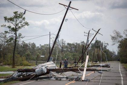 Un hombre pasa por delante de cables eléctricos caídos para llegar a su residencia tras el huracán Laura en Sulphur, Louisiana, el 27 de agosto de 2020 (REUTERS/Adrees Latif(